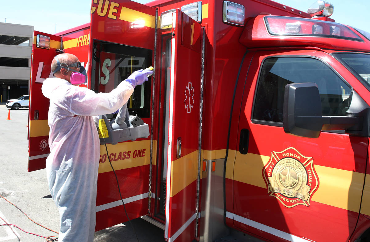 Bill Meeks of Summit Restoration disinfects a Las Vegas Fire Department Paramedic truck on Mond ...