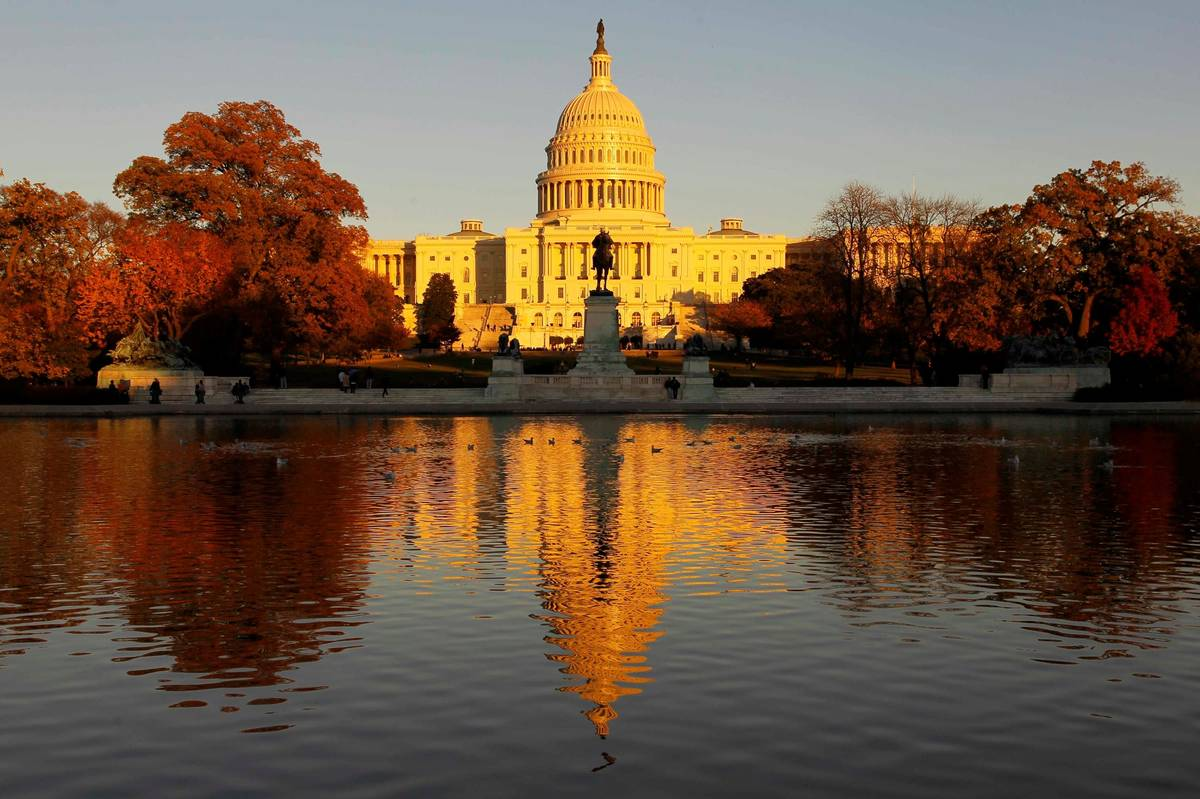 The US Capitol is bathed in the setting sun and seen in the reflecting pool on Capitol Hill in ...