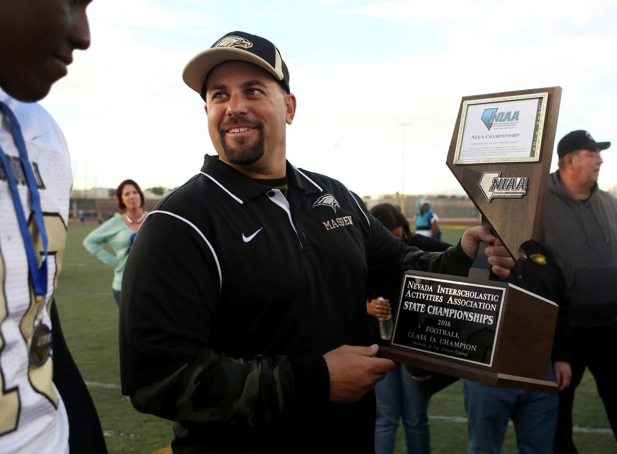 Spring Mountain's Head Coach Aaron Masden holds his team's trophy after winning the class 1A st ...