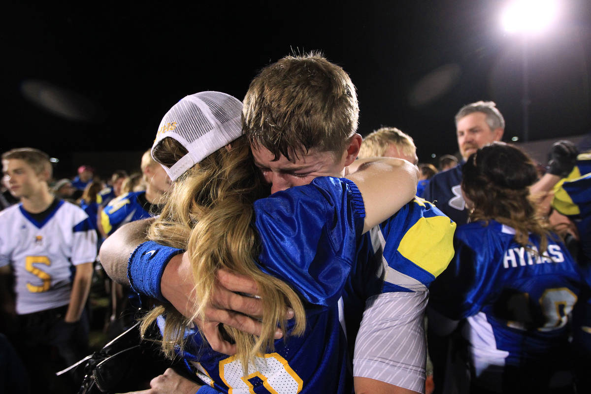 Moapa Valley quarterback Zach Hymas gets a big hug from his mother Becky Hymas after the Pirate ...
