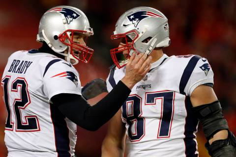 New England Patriots quarterback Tom Brady (12) celebrates with tight end Rob Gronkowski (87) d ...
