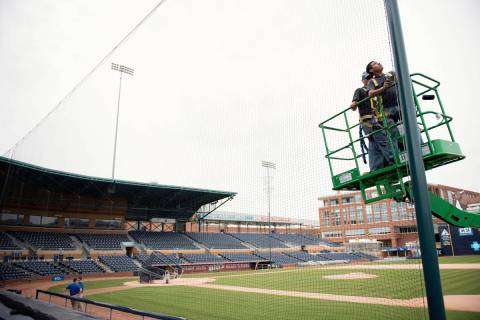 Elias Ruiz, front right, and Steven Woytysiak, both from C&H Baseball, help install a 35-foot-h ...