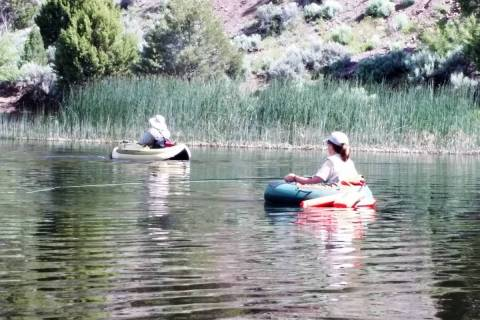 A pair of fly-fishers maintain safe fishtancing while float tubing at Eagle Valley Reservoir be ...