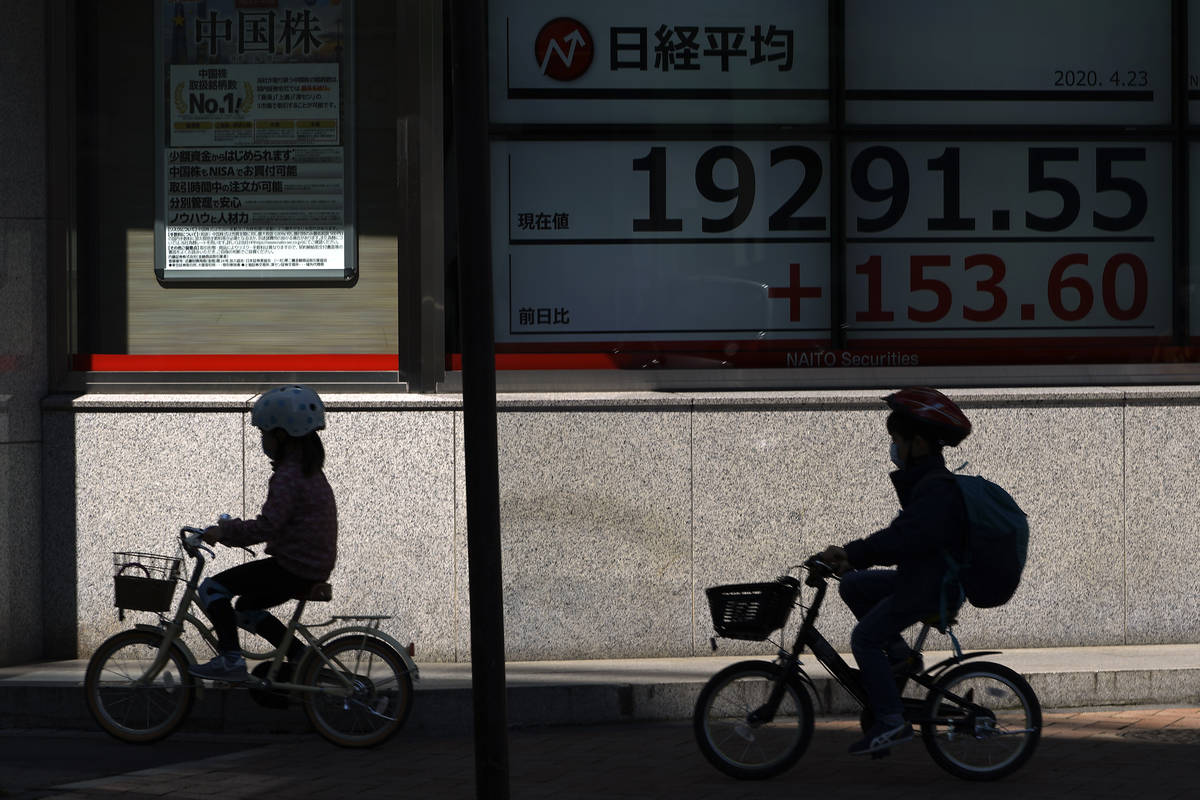 Children wearing masks against the spread of the new coronavirus ride bicycle past an electroni ...