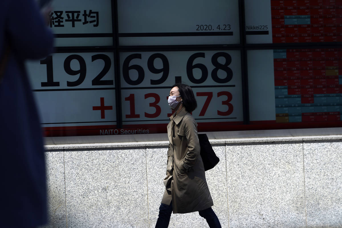 A woman wearing a mask against the spread of the new coronavirus walks past an electronic stock ...