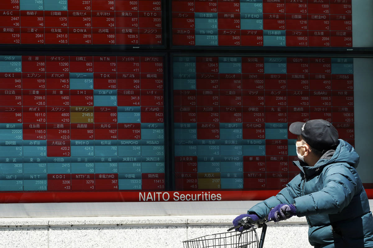 A man wearing a mask against the spread of the new coronavirus looks at an electronic stock boa ...