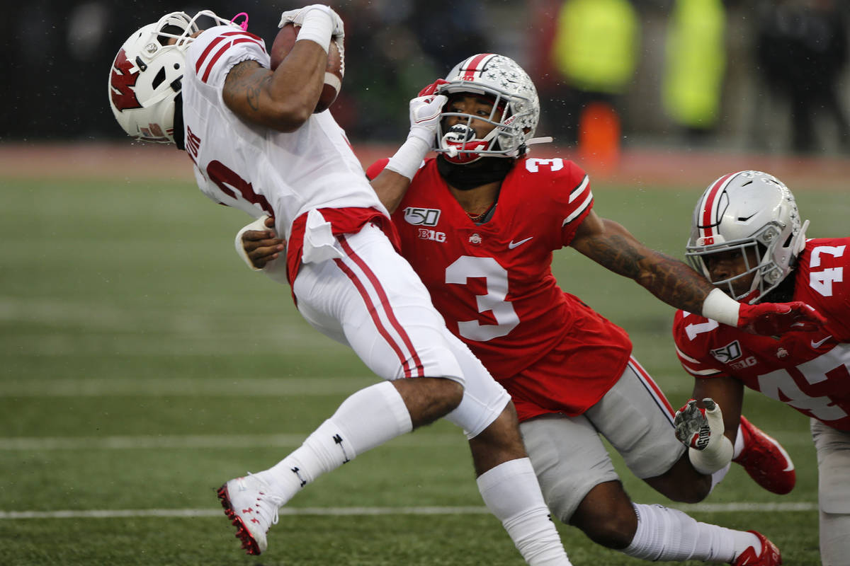 Ohio State defensive back Damon Arnette, right, tackles Wisconsin receiver Kendric Pryor during ...