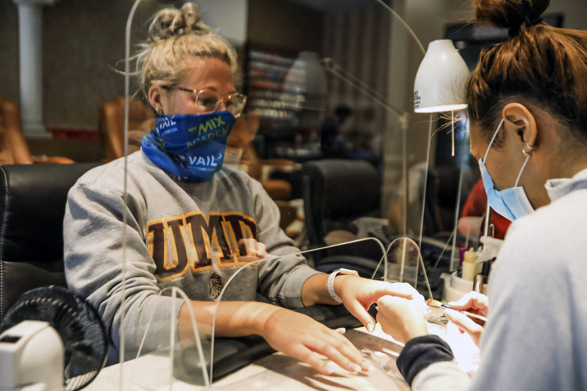 Logan Nash, left, gets a manicure, with all the proper social distancing requirements, includin ...