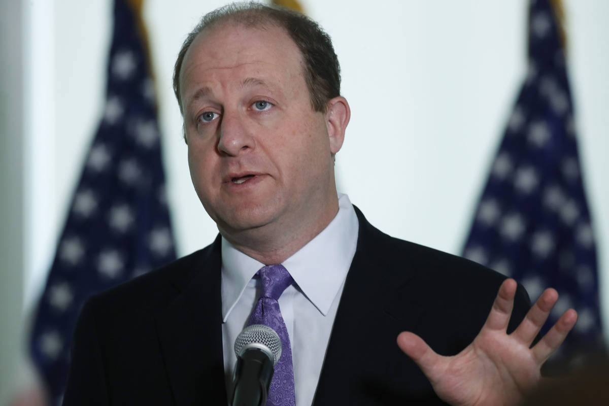 Colorado Governor Jared Polis makes a point during a news conference to update the state's effo ...