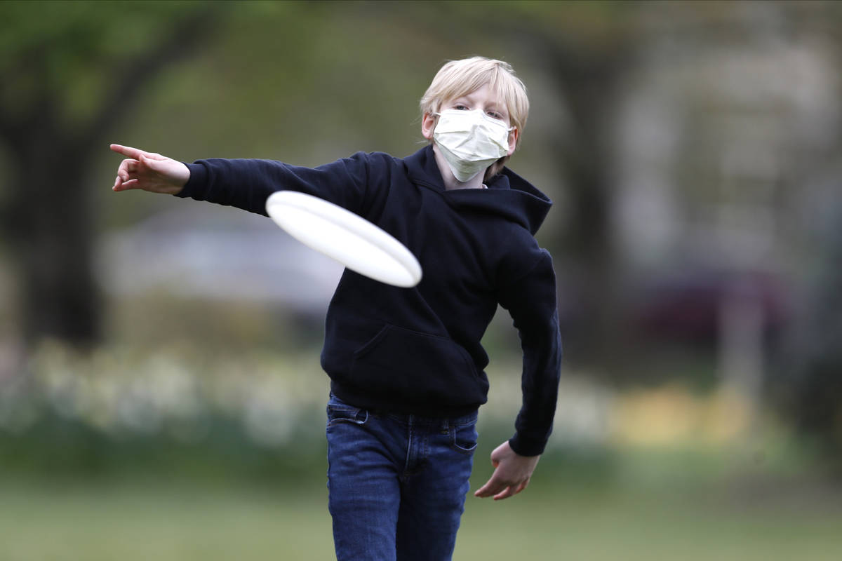 Shawn Cotter, 11, wears a face mask as he throws a Frisbee while playing catch with his father ...