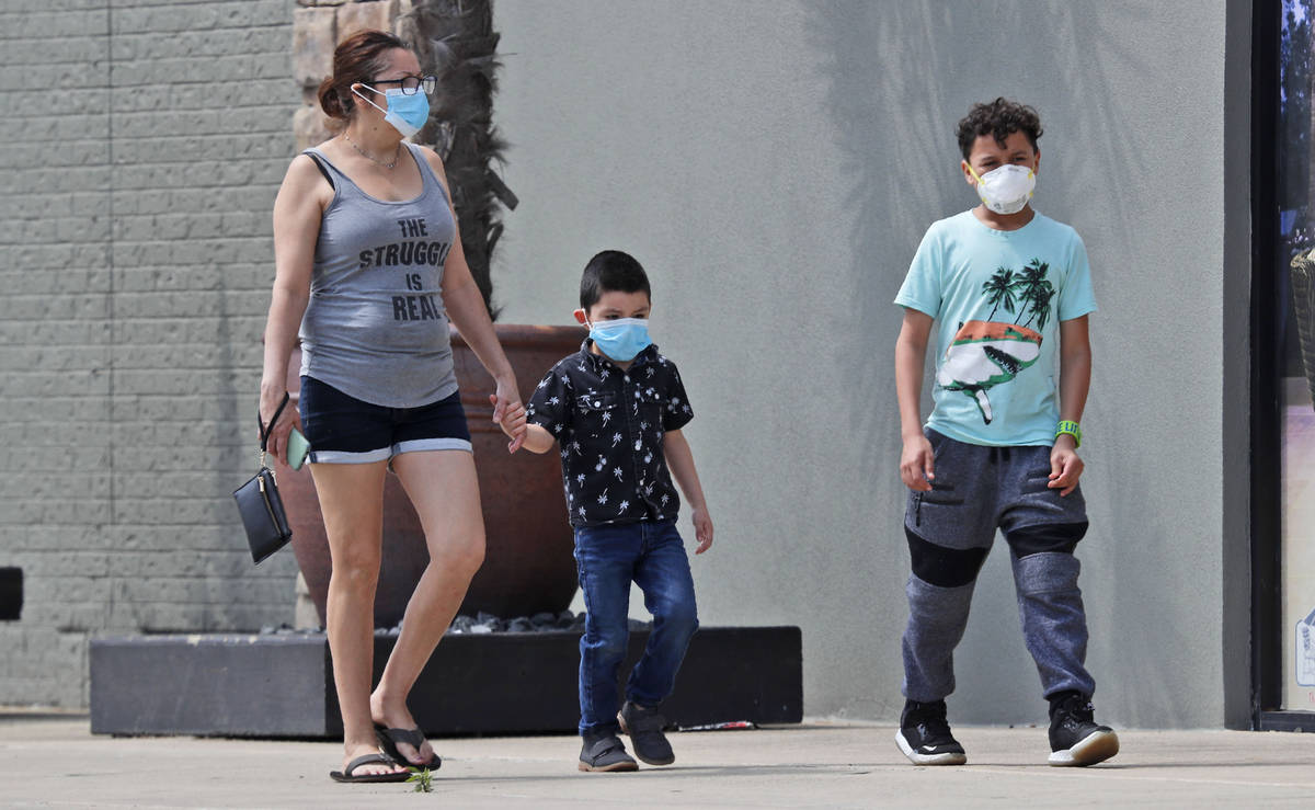 Amid concerns of the spread of COVID-19, a woman and two boys wear masks as they walk at a shop ...