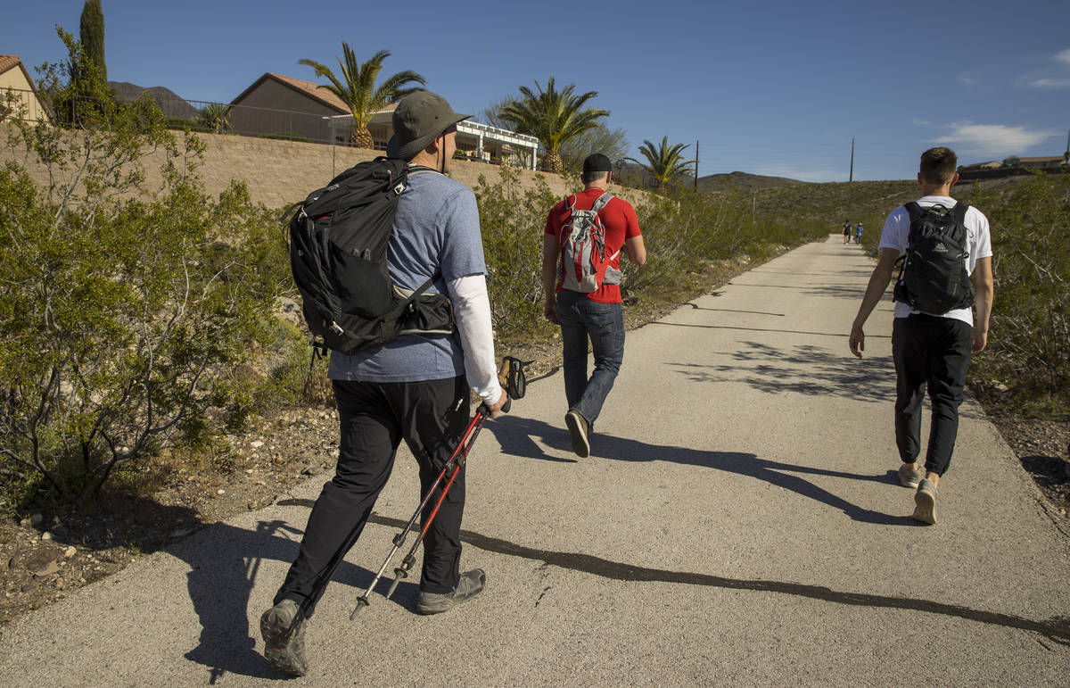 David Koch, left, with brother Michael and son Mason begin a trek back up to their Nevada light ...