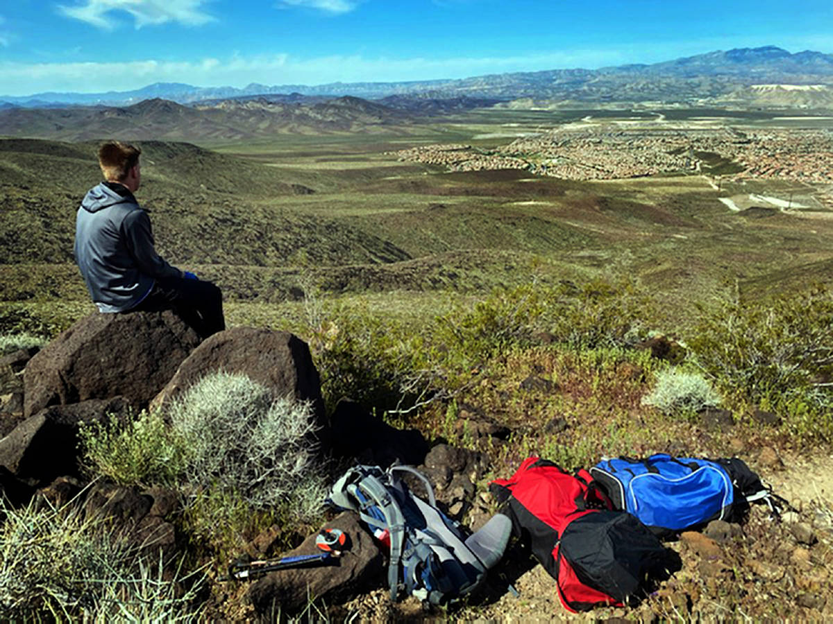 Mason Koch looks down to the Anthem area while atop of Black Mountain to adjust the heart shape ...