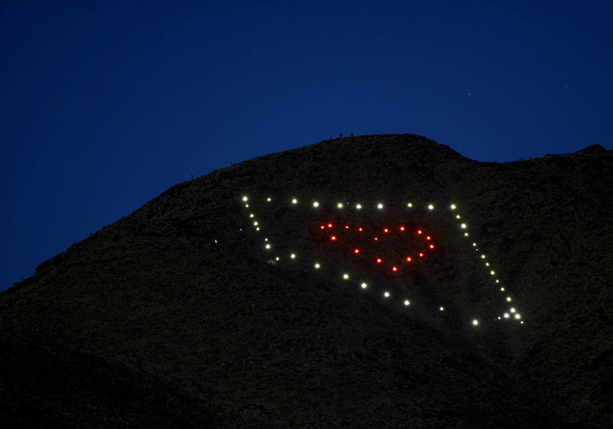 The solar lights come on at dusk from a Nevada light display atop of Black Mountain created by ...