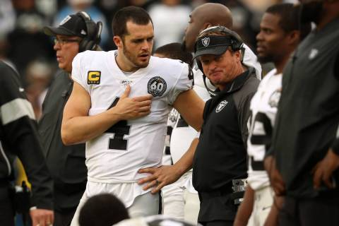 Oakland Raiders quarterback Derek Carr (4) speaks with head coach Jon Gruden on the sideline du ...