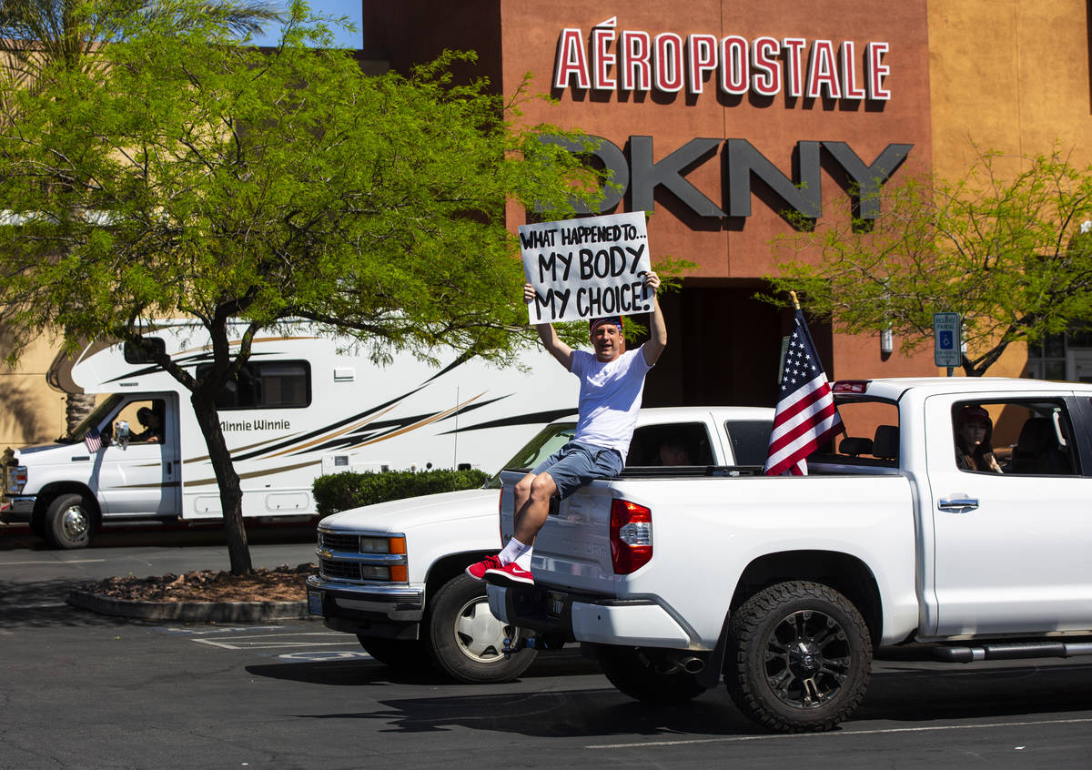 """A man holds up a sign at the Las Vegas South Premium Outlets before participating in a """"ca ..."""