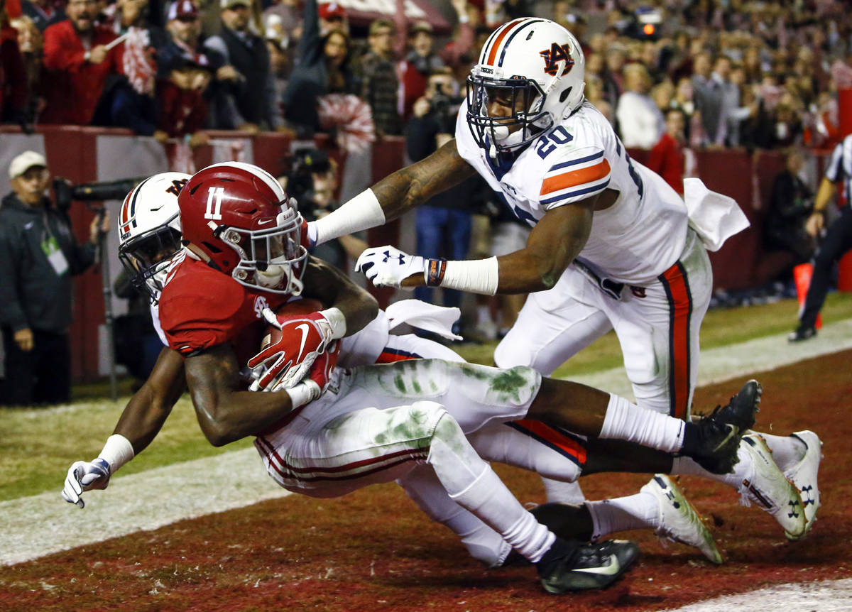 FILE - In this Nov. 24, 2018, file photo, Alabama wide receiver Henry Ruggs III (11) catches a ...