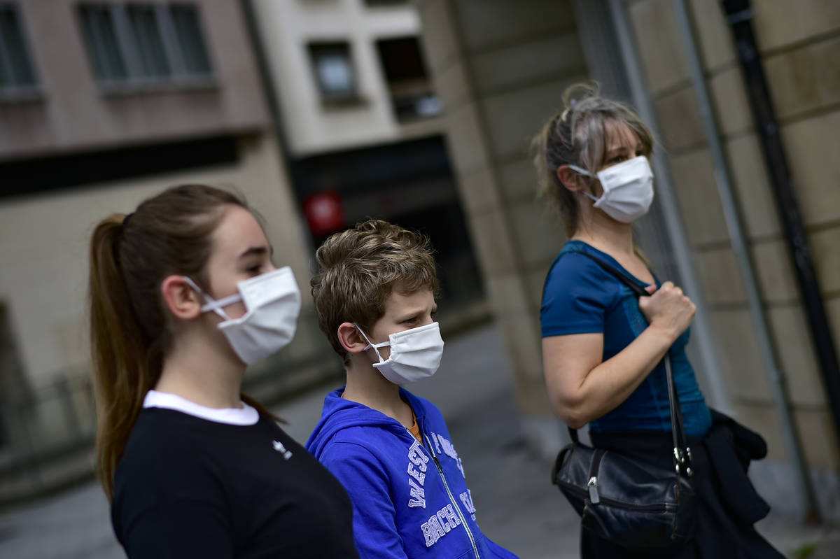 A family wearing face mask to protect of the coronavirus go for a walk, in Pamplona, northern S ...