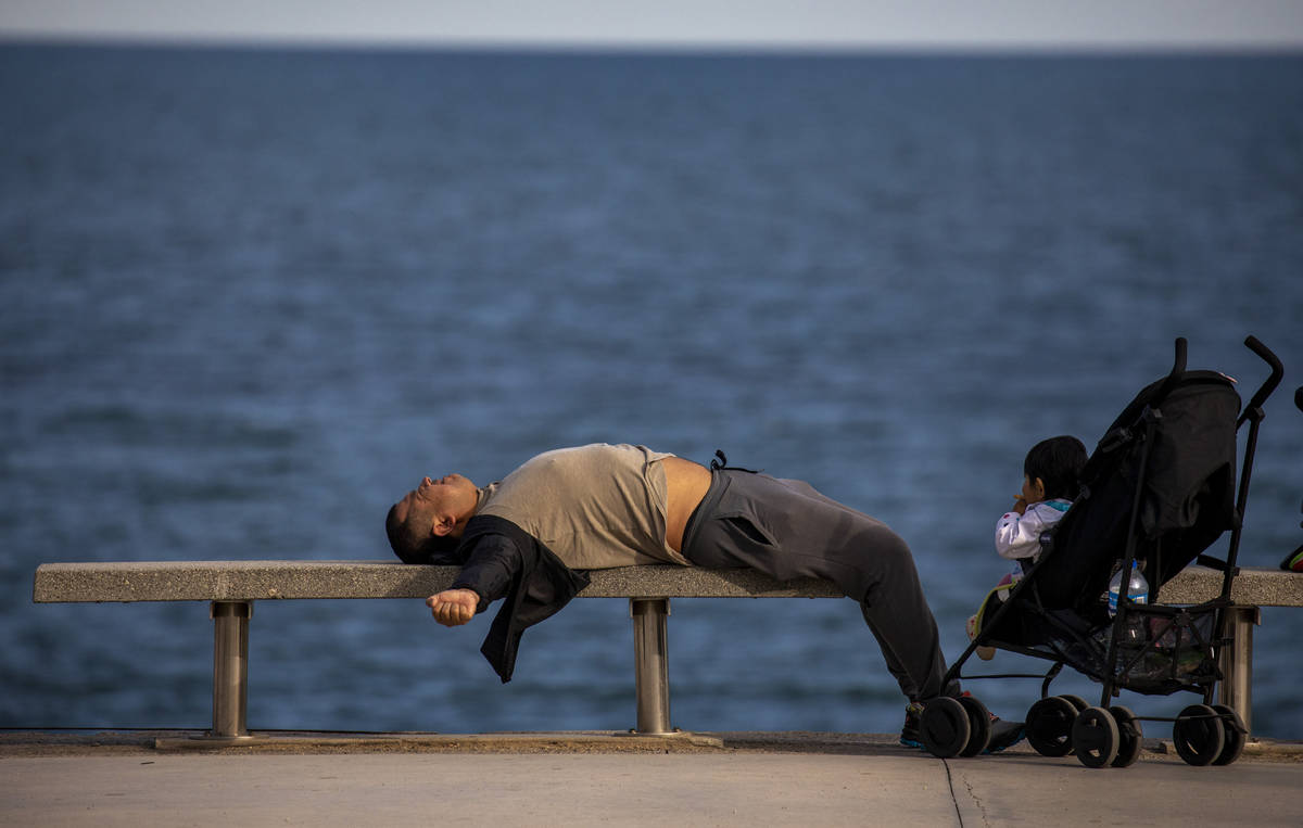 A man lies on a bench in front of the Mediterranean sea in Barcelona, Spain, Sunday, April 26, ...