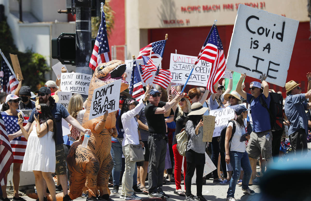 Protesters stand along Mission Blvd. during A Day of Liberty rally in Pacific Beach in San Dieg ...