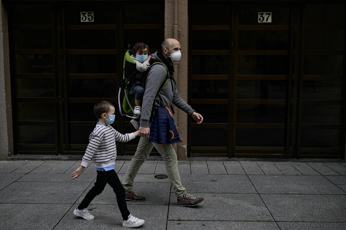 A father with his children wearing face mask to prevent the coronavirus go for a walk at Carlos ...