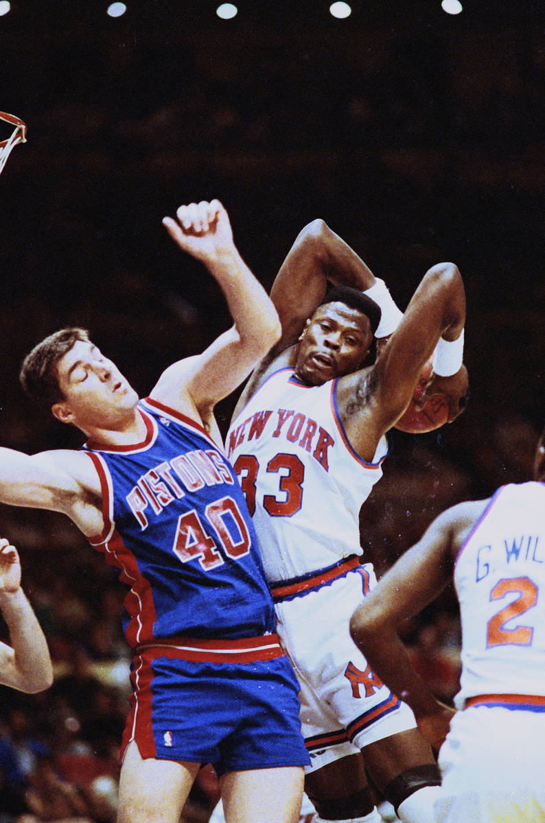 New York Knicks Patrick Ewing grabs a rebound away from Detroit Pistons Bill Laimbeer in the fi ...