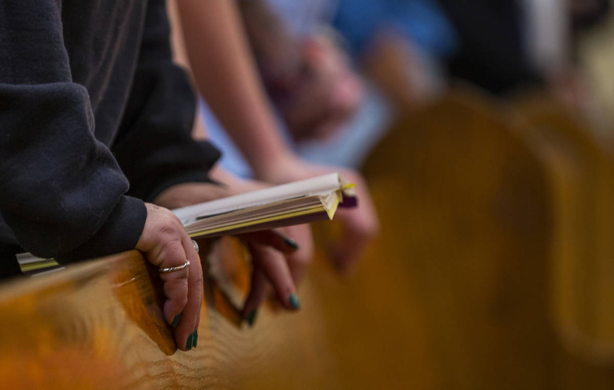 Parishioners pray during Sunday Mass at St. Anne's Catholic Church where they were asked to use ...