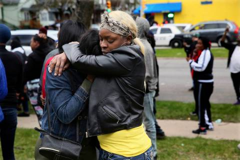 Bystanders comfort each other at the scene of a shooting where five people were killed in Milwa ...