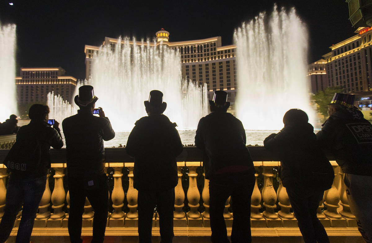 People enjoy the Bellagio fountain show on the Strip on Tuesday, Dec. 31, 2019, in Las Vegas. ( ...