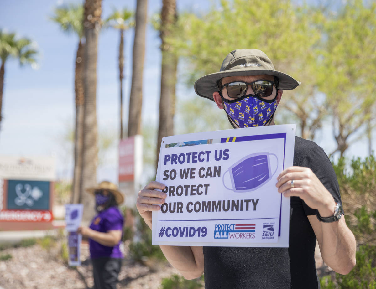 Jason, a Local SEIU 1107 member, holds a sign in protest of unsafe working conditions during th ...