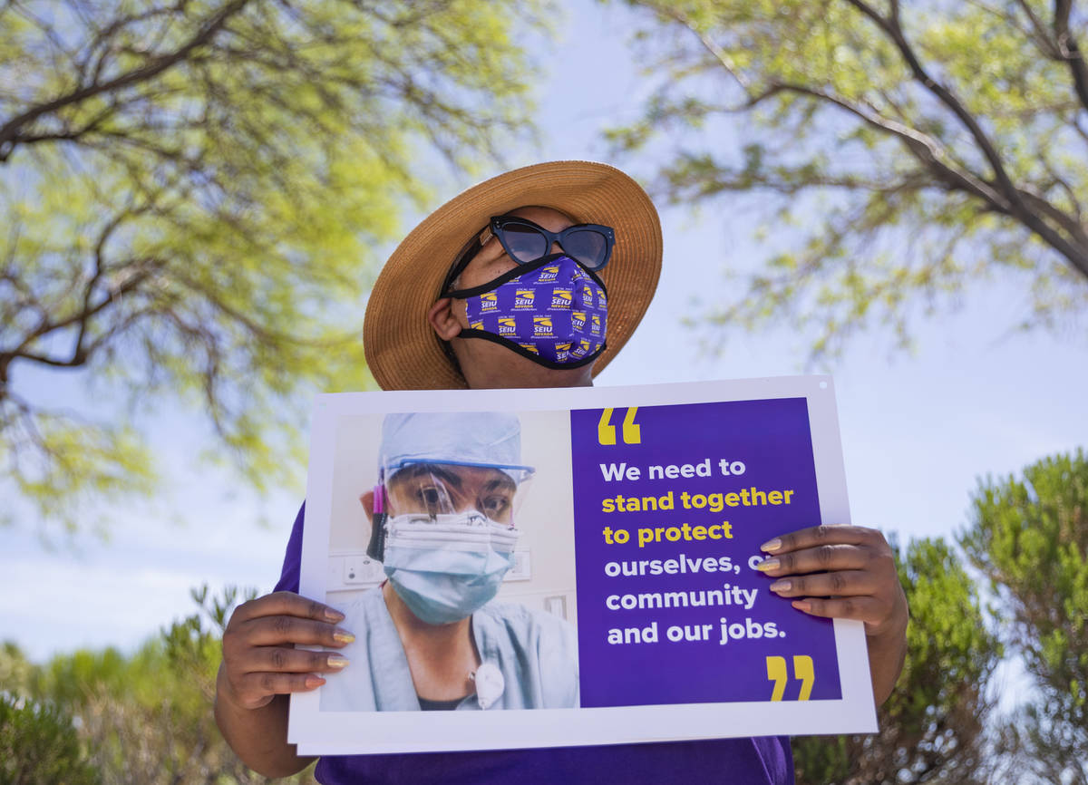 Zavia Norman, private sector vice president of Local SEIU 1107, holds a sign in protest of unsa ...