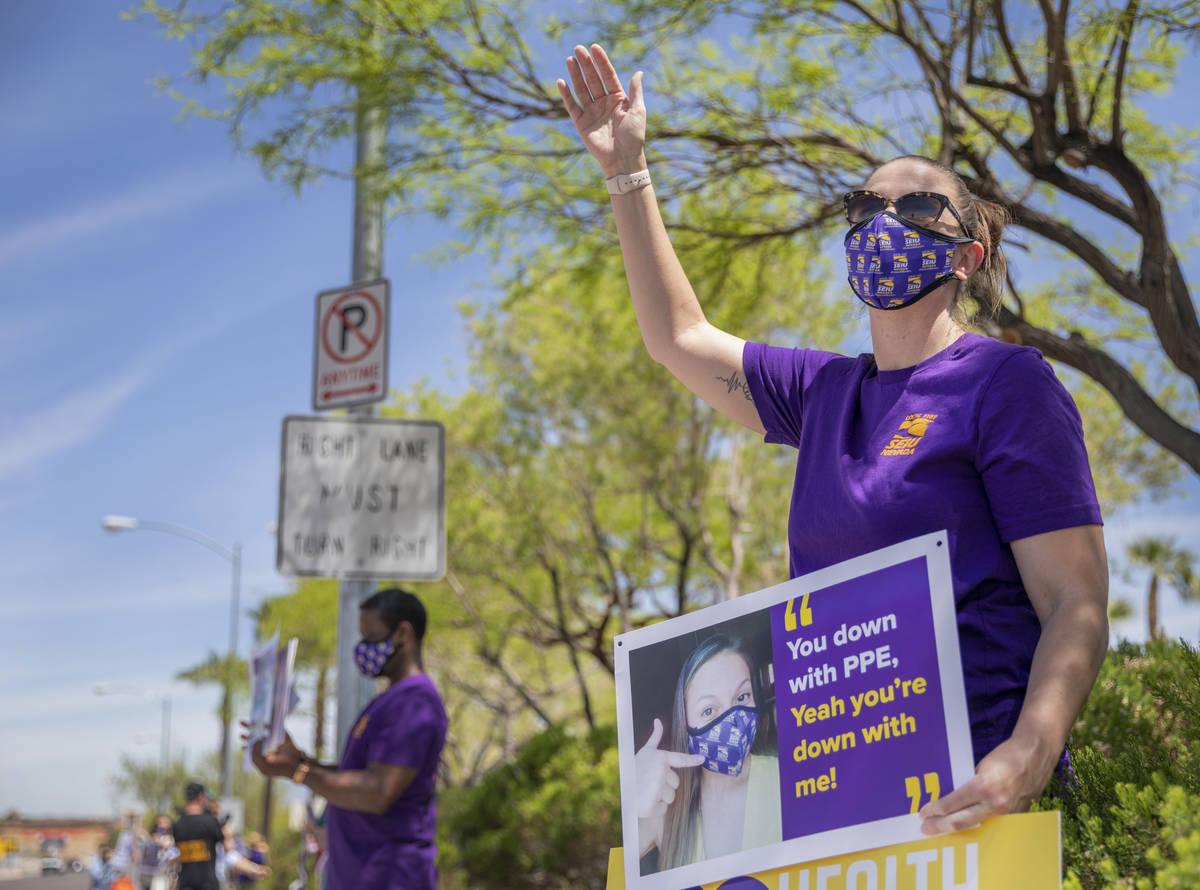 Jody Domineck, Local SEIU 1107 member, waves at cars that honk as Local SEIU members protest un ...