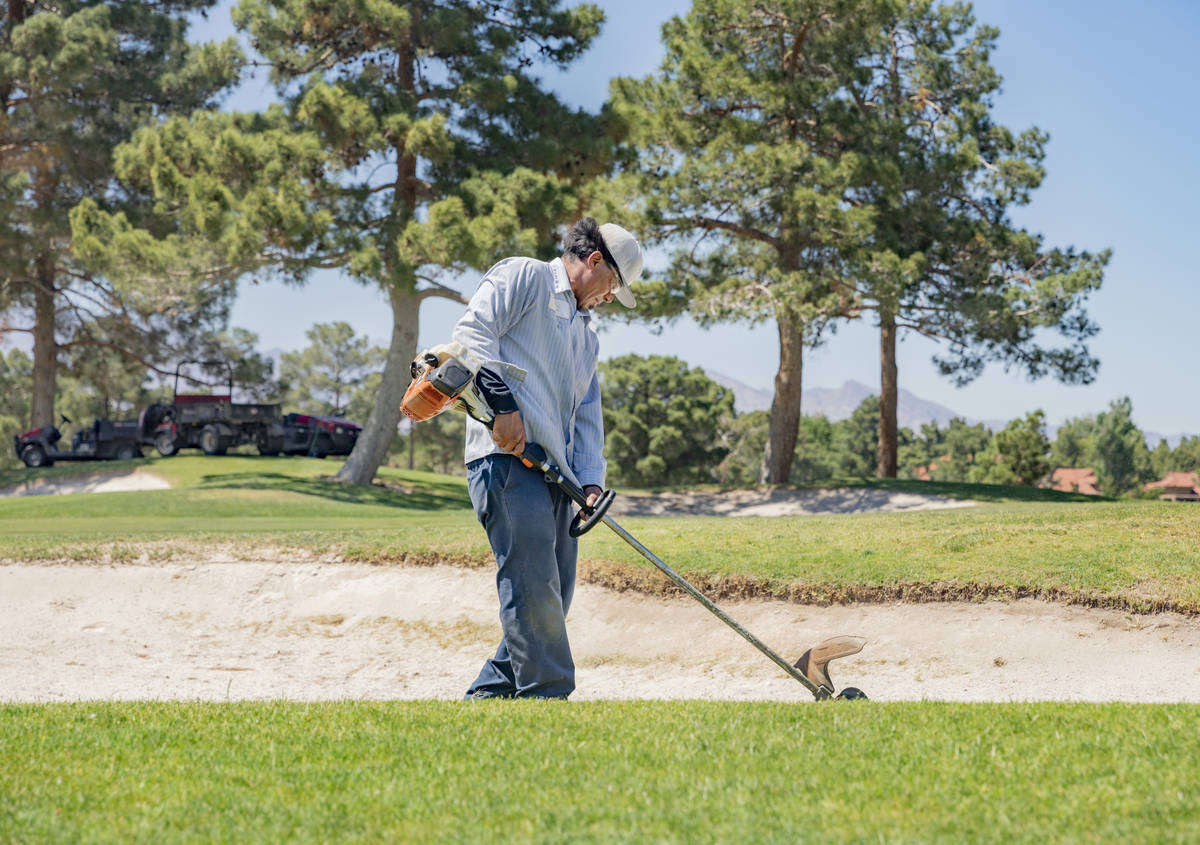 Groundskeeper Jose Gallegos edges the sand bunkers in preparetion for the opening of the Spanis ...