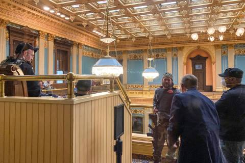 Armed protesters stand in the gallery of the Michigan State Senate chambers at the State Capito ...