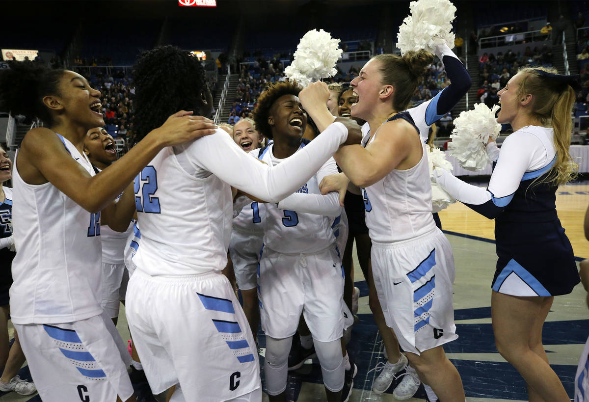 The Centennial Bulldogs celebrate a 74-65 overtime win over Liberty for the NIAA state basketba ...