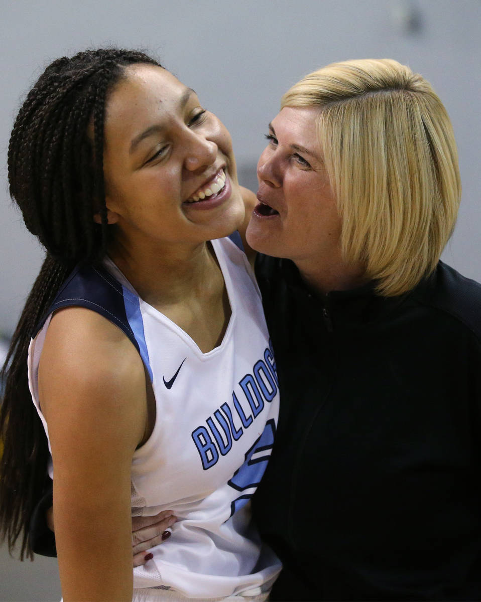 Centennial's Jade Thomas celebrates with an assistant coach after her shot at the buzzer forced ...
