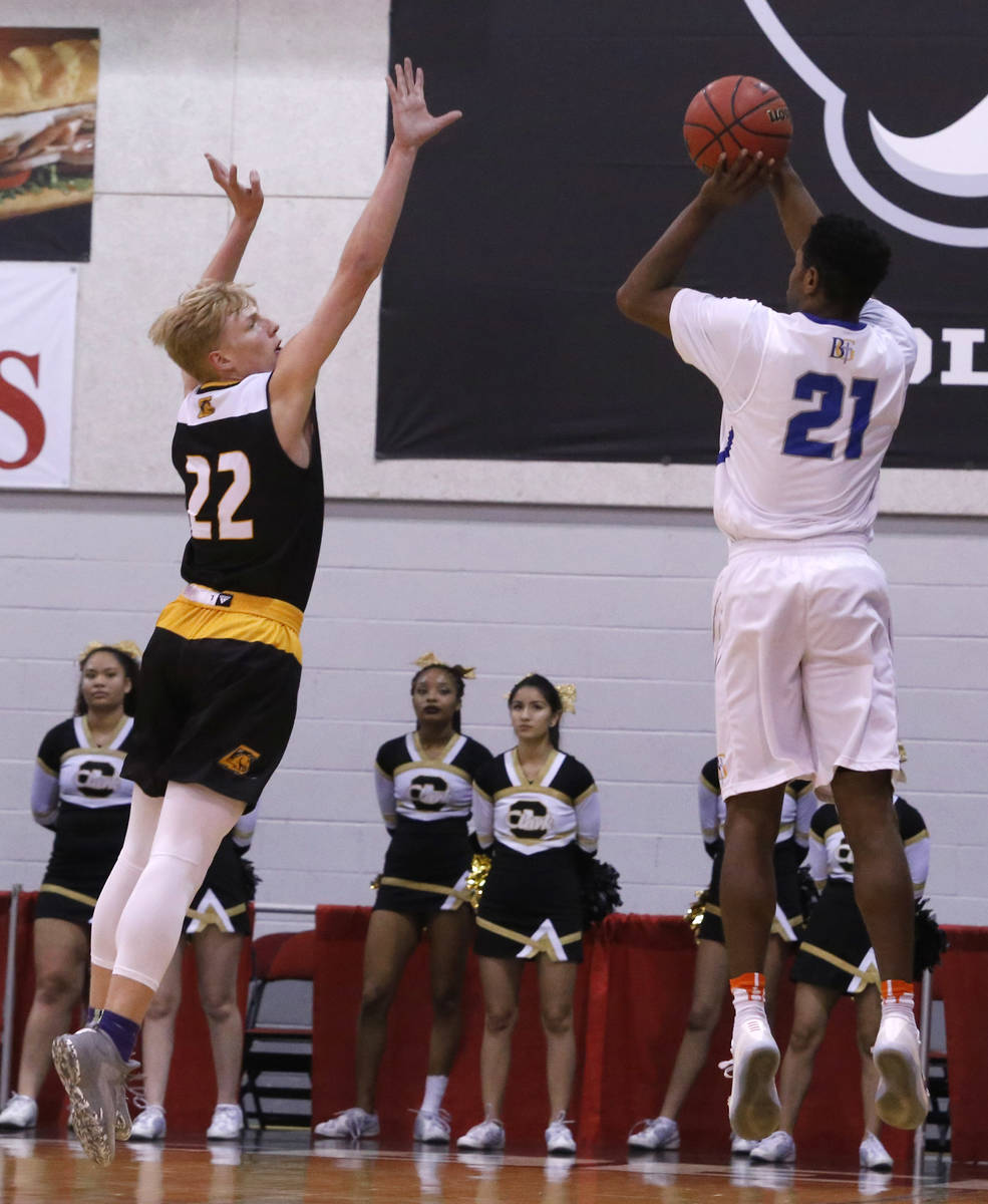Bishop Gorman's Christian Popoola (21) shoots over Clark's Trey Woodbury (22) during the first ...