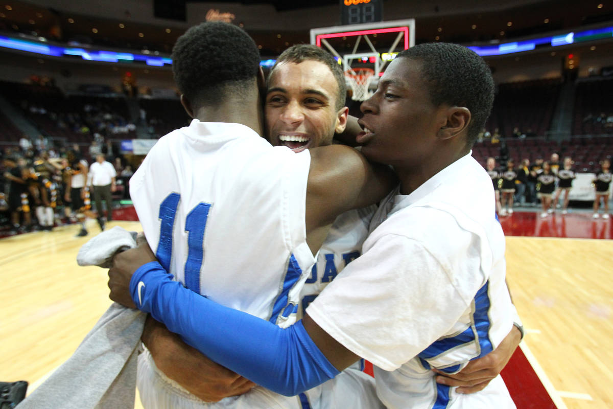 Desert Pines players, from left, Malik Davis, Julian Jacobs and Tim Hough celebrate after defea ...