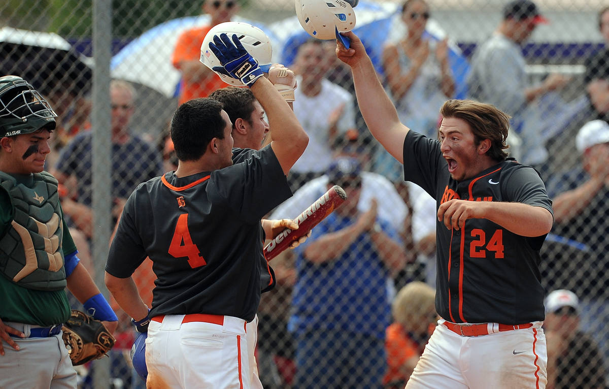 Bishop Gorman first baseman Austin Cram (24) high fives teammates home plate as catcher Ty Burg ...