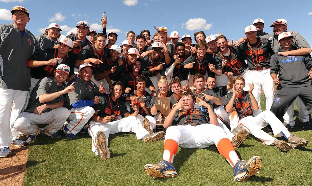 Bishop Gorman players and coaches celebrate with the NIAA trophy after defeating Green Valley 6 ...