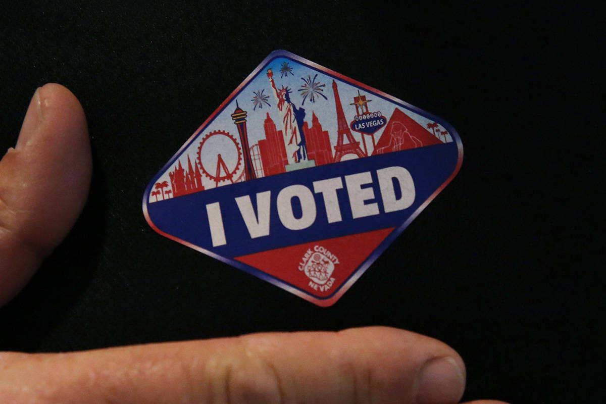 """Kirk Rossmann shows off his """"I Voted"""" sticker after casting his ballots at a polling station at ..."""
