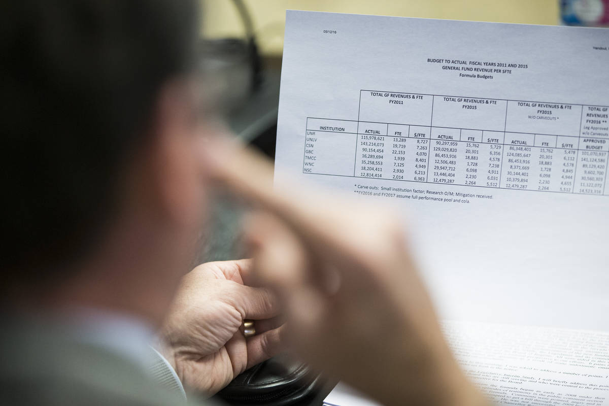 A member of the Board of Regents looks at a budget from final years 2011 and 2015 during a spec ...