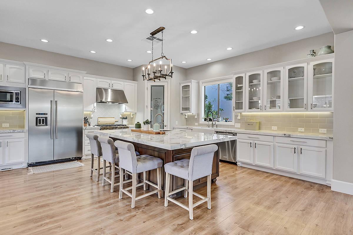 Huntington & Ellis The kitchen features KitchenAid appliances, a large center island and porcel ...