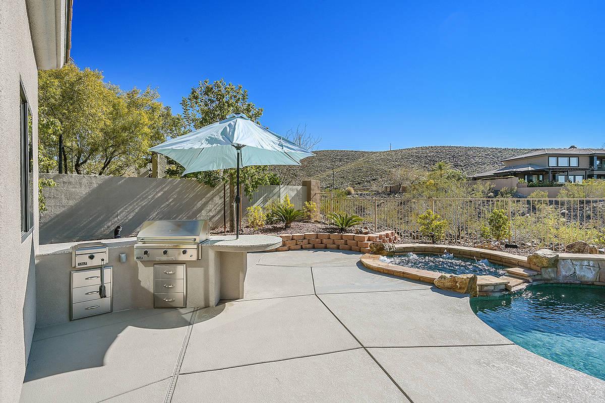 The backyard has an outdoor kitchen. (Huntington & Ellis)