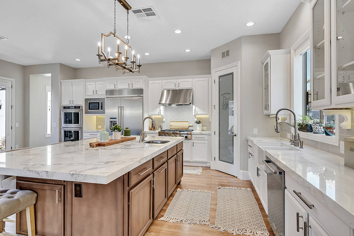 The kitchen has a large center island with seating. (Huntington & Ellis)