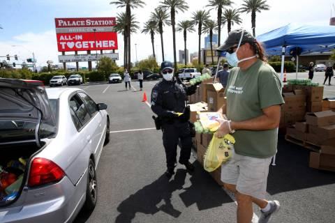 Brian Fisher, 53, of Las Vegas, right, Nevada Highway Patrol Sgt. Brady Knapp and volunteers wi ...