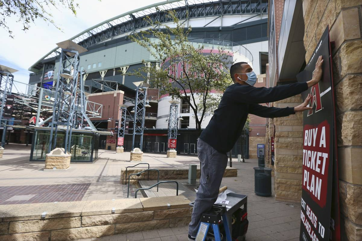 Joey Rodriguez, of Image Craft, installs an advertising banner in front of Chase Field Thursday ...