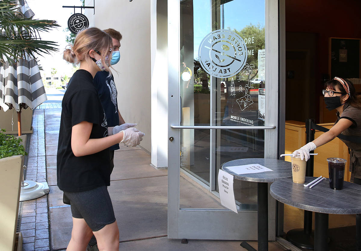 Nyah Klee, right, delivers drinks to Nick Dugan and his friend Emily Hanson, both of Henderson, ...