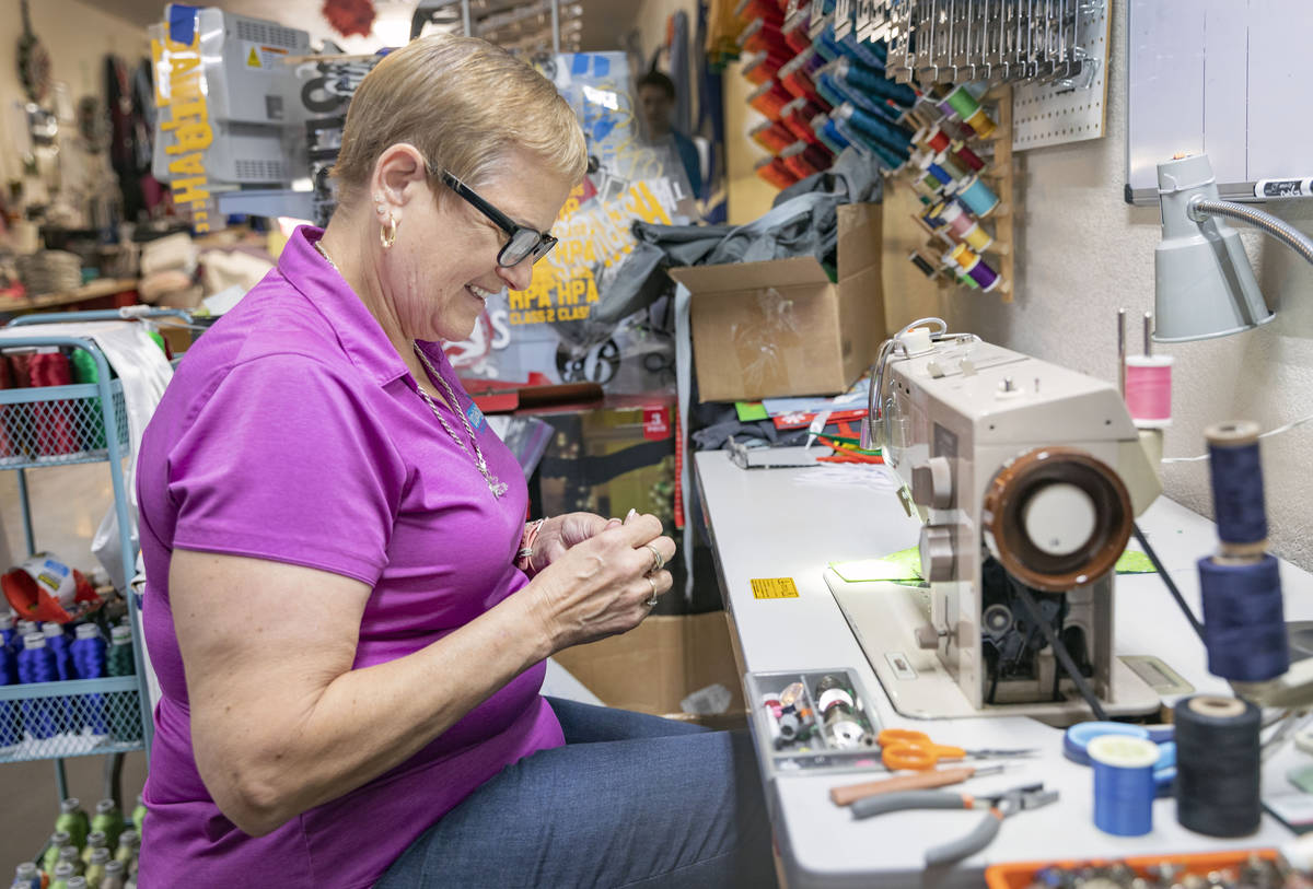 Michele Walker, owner of Imaginations Unlimited, sews a cloth face covering, in her embroidery ...