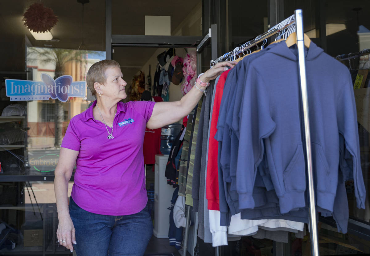 Michele Walker, owner of Imaginations Unlimited, organizes clothes out on the sidewalk to visua ...